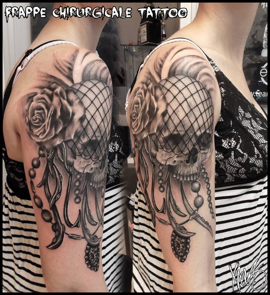 black and grey skull tattoo on upper arm