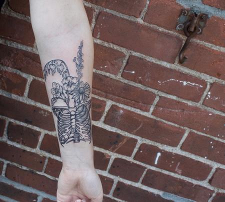 Ben Licata - Black illustrative rib cage with wild flowers tattoo on forearm